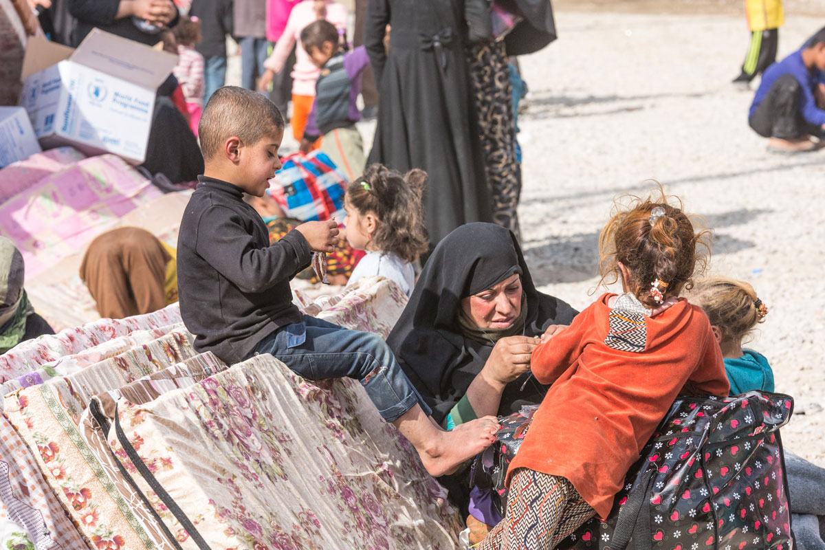 A family waits for assistance in Debaga Camp, northern Iraq.