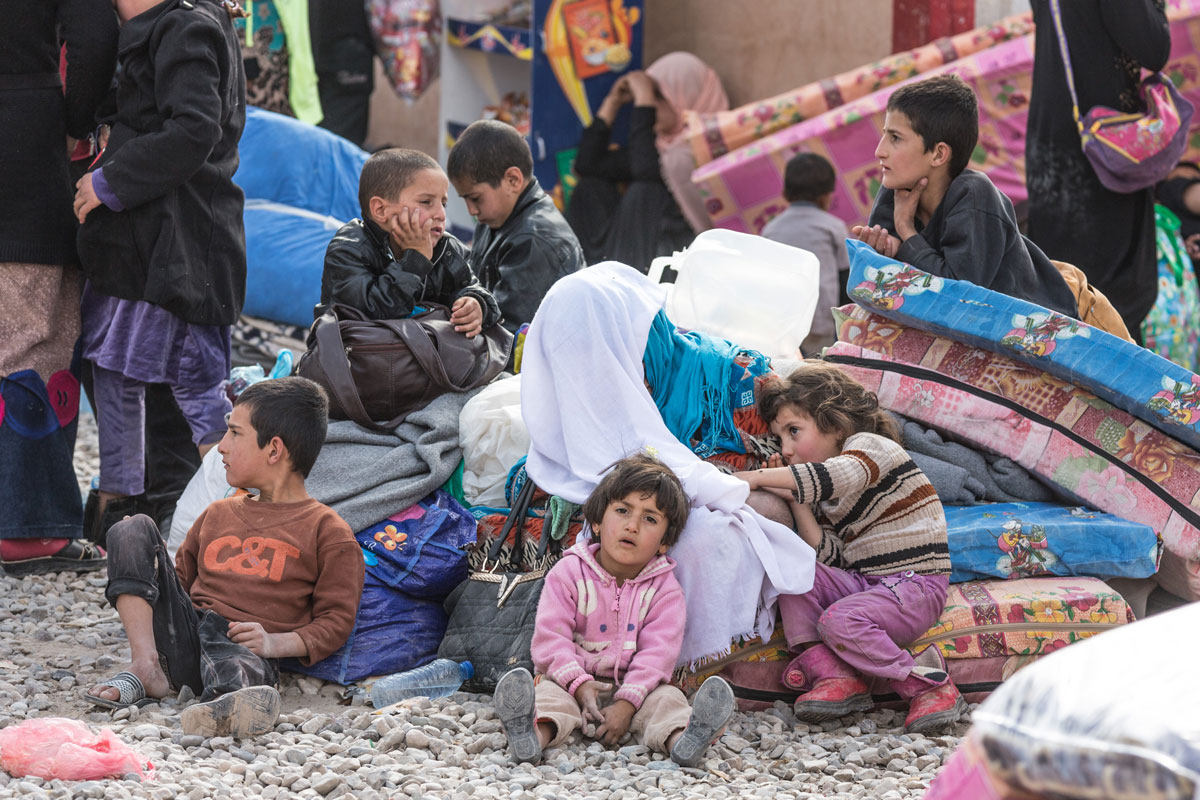 Children who have recently arrived at Debaga Camp after fleeing Mosul wait outside on mattresses. Without enough tents, many have been sleeping here and in corridors of a local school that is within the camp's boundaries.