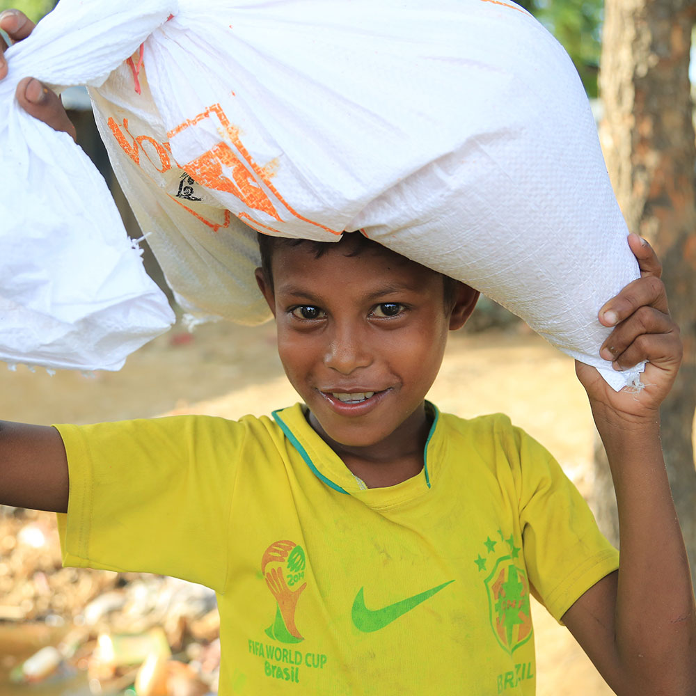 Rofi and family receiving their two-week food supply at a World Vision distribution site