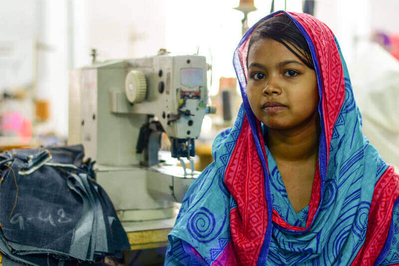 15 year old Bithi lacks child rights, and is forced to spend her days sewing jeans for high income countries