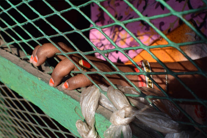 hand clenches a cage, highlighting the importance of child rights awareness