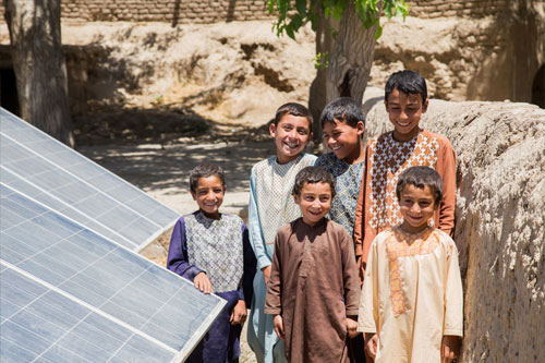 Children stand by a solar panel that powers a drinking water decontamination system in the Langar district in Afghanistan.