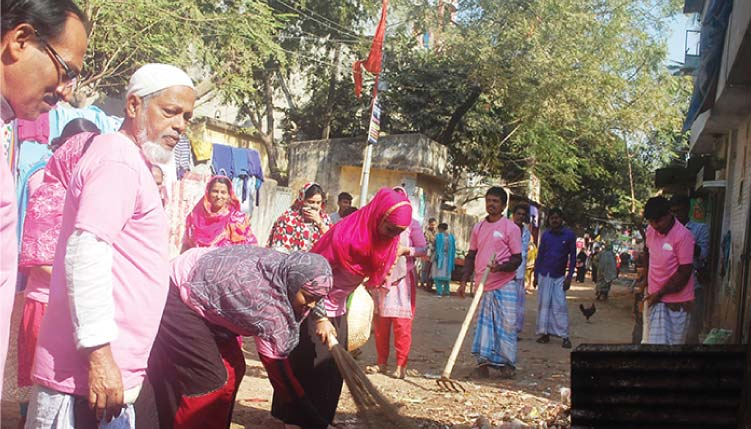 Women sweep the streets with straw brooms