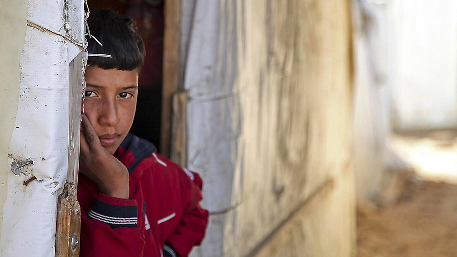 A boy peers around a door