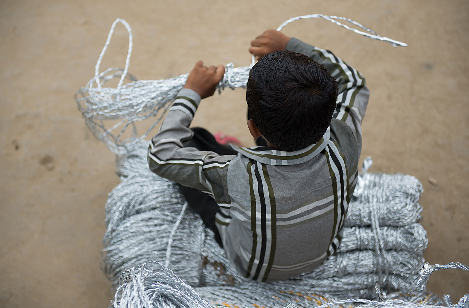 Boy who is a victim of child labour sits on a bundle of ropes