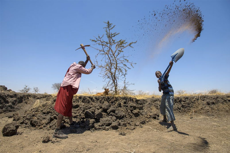 Two farmers working in a dry, dusty landscape