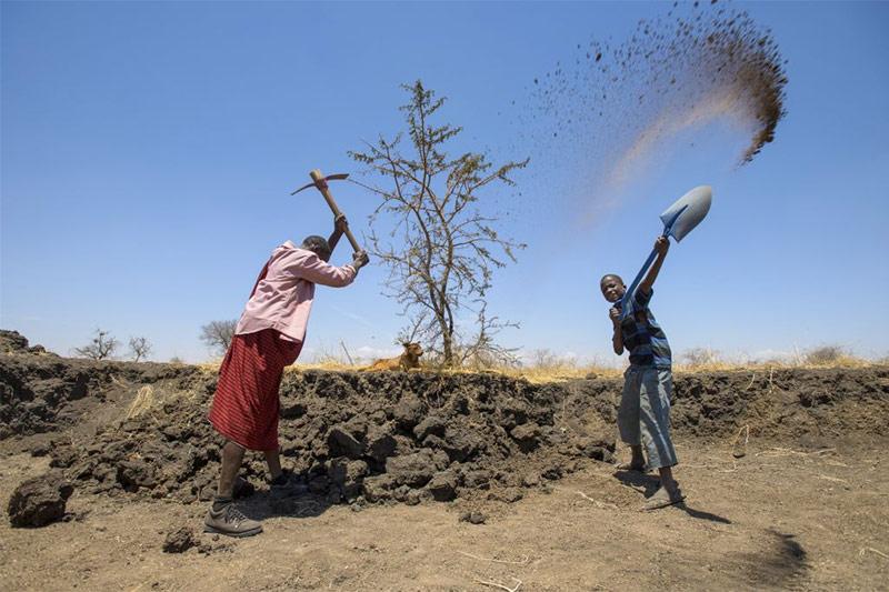 Two farmers working in a dry, dusty landscape