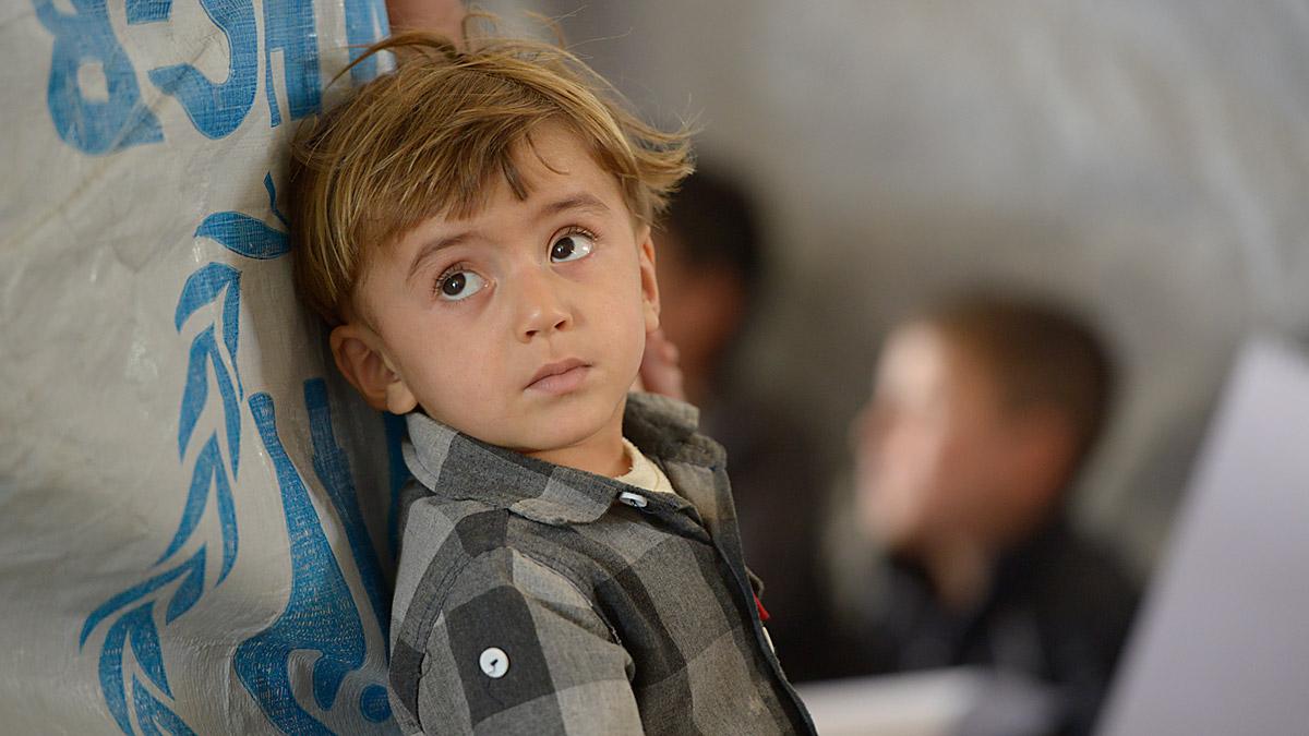 Syrian child peers around a door