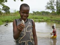 Benjamin, aged nine, proudly displays a fish growing in one of his village's fish farms in South Sudan.