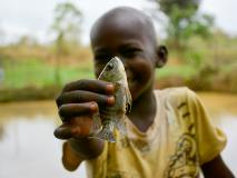 Young Mopao shows off one of the fingerlings found swimming in the fish farms of South Sudan.