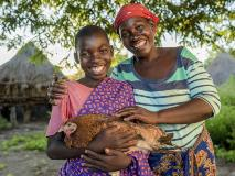 Resheal and his mum Esnart with one of their chickens in Zambia.