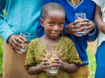 As a little brother to a sponsored child, Emmanuel and his community benefit from clean drinking water supplied by a World Vision tap near their home in Kisaro, Rwanda.