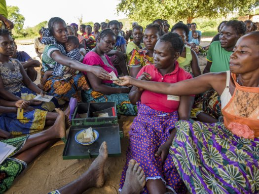 Members of this community group in Zambia gather around their savings box to pay in their contributions.