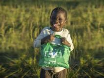 Adam, aged five, from Zambia, takes special care of his family's first aid kit.