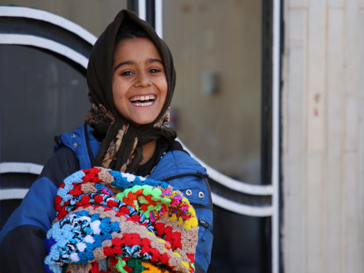 Smiling girl with emergency blanket gift