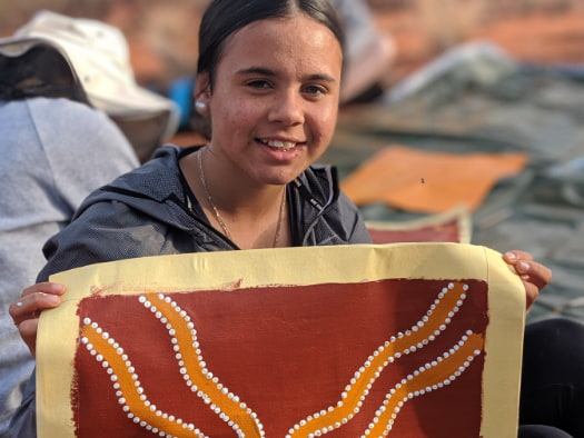 A participant in World Vision's Young Mob program displays her artwork.