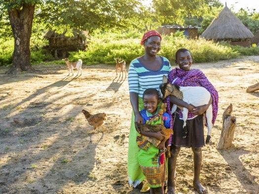 Esnart and her children with a goat and a chicken they received from World Vision.