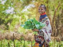 Esther, aged nine, with kale harvested from her community garden in Kenya.