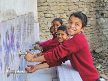 Students demonstrate how to wash their hands outside their school's toilet in Nepal.