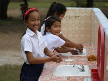 Young Cambodian students demonstrate how to wash their hands with their newly installed handwashing stations.