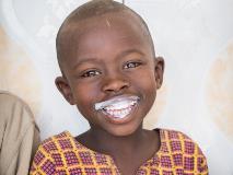 Amani drinks milk at the Tare Milk Collection Centre in Rwanda.