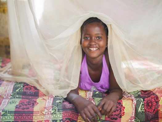 Isata, aged 12, from Sierra Leone, says she feels safe sleeping under her mosquito net.