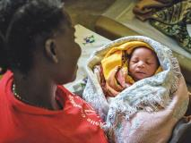 A mother lovingly watches her newborn sleep peacefully at a health centre in Uganda.
