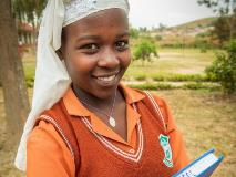 Sarah, from Zimbabwe, holds a book that shares her love of learning and a message – stay in school.