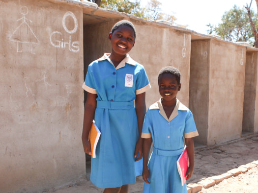 Joan (left) and Shyline (right) in front of their new toilets at their school in Hwange, Zimbabwe.