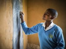 In Rwanda, 16-year-old Isabelle solves a maths equation on a blackboard her parents set up at home so she can do extra study.