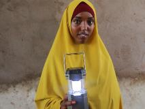 In Somalia, Rahma uses her solar lantern for light to study and walk outside safely when darkness falls.