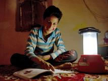 In India, 12-year-old Aman uses his family's solar light to study and walk outside safely when darkness falls.