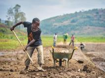 In this community in Rwanda, a farmer digs in preparation for a fish pond.