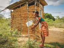 Kodzo, aged 12, washes her hands at her family's new toilet and handwashing station in Kenya.